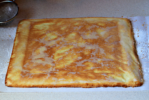 fruit squares with cream cheese filling recipe with step by step pictures, before you remove your fist cake layer from the oven, lay a sheet of parchment paper on your working surface and dust it lightly with some confectioners' sugar, when baked, invert the cake layer onto the paper