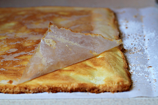 fruit squares with cream cheese filling recipe with step by step pictures, remove the top paper, let cool, line the baking pan with parchment paper again, fill it with the remaining batter and bake it, when baked, leave that cake layer in the baking pan and do not remove it, just let it coll, that will be the bottom layer of our cake
