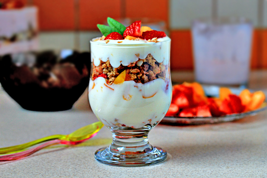 fruit yogurt parfaits recipe with step by step pictures, line up four glasses or parfait goblets, layer spoonfuls of granola, yogurt, and fruit until the glasses are full, place some fruit on top