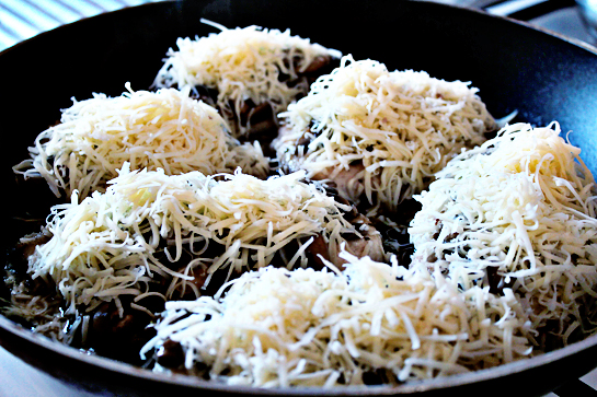 chicken with mushrooms and cheese step by step recipe with ingredients and pictures, chicken fillets covered with mushroom sauce and shredded cheese in a large frying pan, skillet