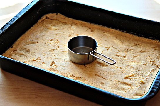 Caramel apple cheesecake cookie bars recipe with step by step pictures. Spreading bottom cookie layer batter using a stainless steel measuring cup.