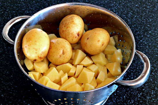 Scrub clean 4 potatoes. Peel and cube the remaining potatoes.  Boil the potatoes in a large pot of water until soft.