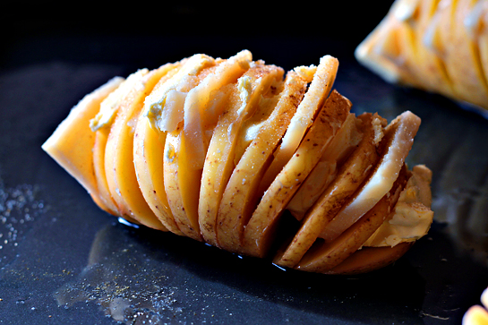 Scalloped hasselback potatoes step by step picture recipe. Slice the butter and Parmesan. Next, open the potatoes' crevices and shove the Parmesan and butter, alternating between the two.