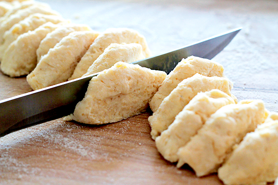Garlic and cheese biscuits recipe with step by step pictures. Log of dough cut into even pieces.