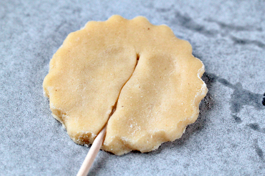 Pie pops recipe with step by step pictures. Line a baking sheet with parchment paper, Place the dough circle onto the sheet. Press down a lollipop stick or a wooden skewer in the dough. Pinch the dough a little to cover the stick.