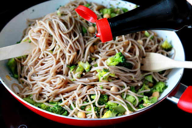 broccoli, chickpeas and garlic whole wheat spaghetti recipe, combining and drizzling with soy sauce