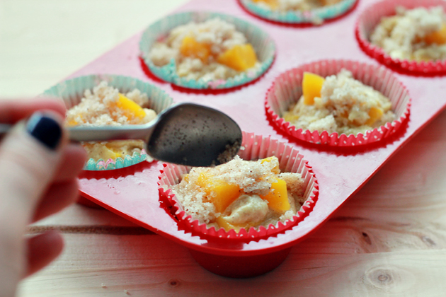 adding streusel topping on top of peach cobbler muffins