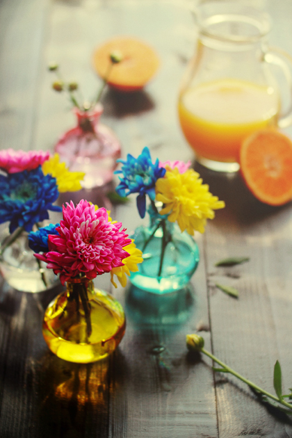 flowers in colorful vases on dark wood surface