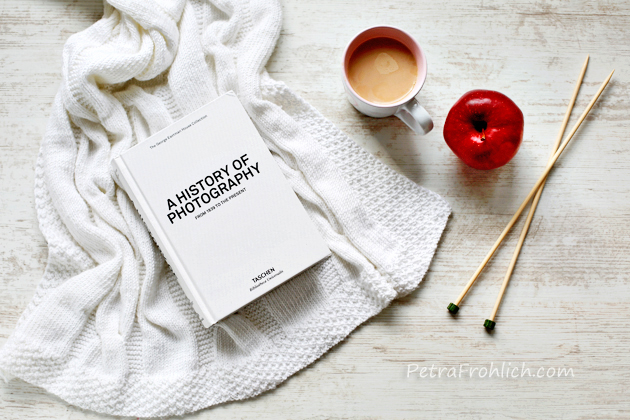 white knit cable blanket, a book, a mug with milk coffee, an apple and knitting needles on a table